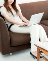 ソファでノートパソコンを使う女性
