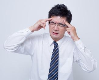 頭痛がつらく、こめかみを押さえる男性