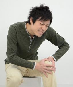 ひざが痛くてうずくまる男性