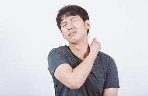 首の痛みに顔をゆがませる男性